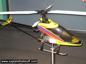 A yellow radio-controlled helicopter mounted as a science museum exhibit.
